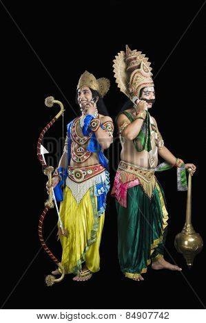 Two actors dressed-up as Rama and Ravana and using mobile phone