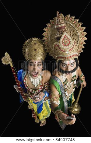 Two stage artists dressed-up as Rama and Ravana and holding mobile phones