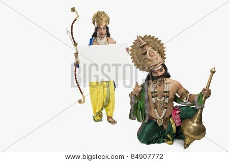 Two stage artists dressed-up as Rama and Ravana and holding a blank placard