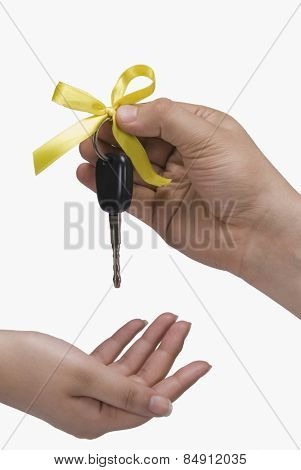 Close-up of a person's hand giving a car key to another person