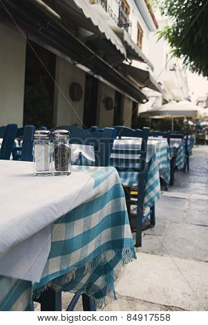Tables and chairs at a sidewalk cafe, Athens, Greece