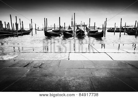 Gondolas Moored In Front Of Pavement Bw
