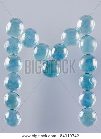 Close-up of marble balls arranged in the shape of letter M