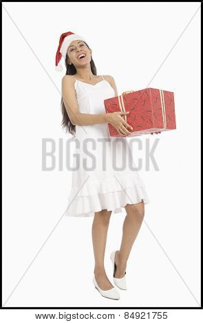 Woman wearing a Santa hat and holding a Christmas present