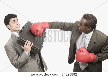 Businessman defending himself from the punch of his colleague