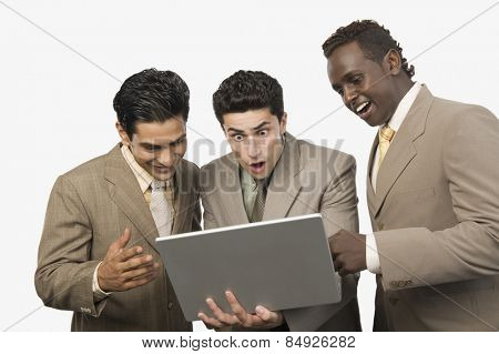 Three businessmen standing with a laptop