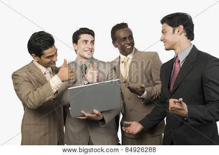 Four businessmen smiling in front of a laptop