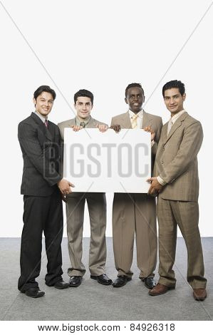 Portrait of four businessmen showing a blank placard