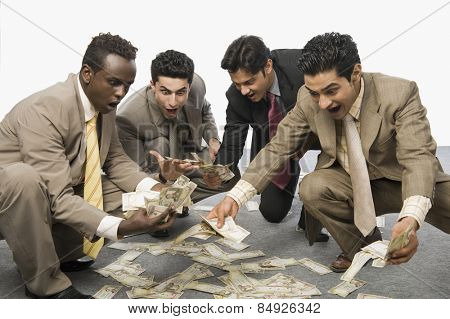 Four businessmen crouching and holding currency notes