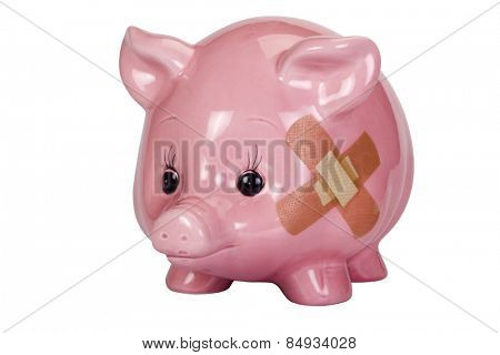 Close-up of a piggy bank with an adhesive bandage