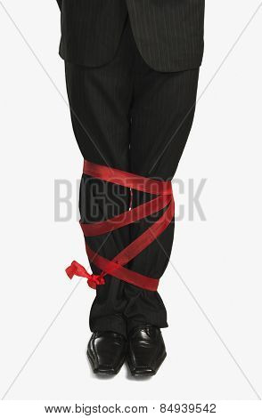 Businessman's legs tied up with a ribbon
