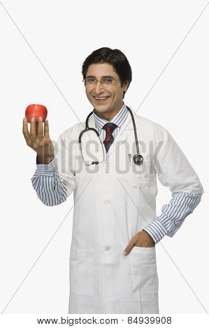 Portrait of a doctor holding an apple and smiling