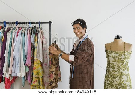 Tailor working in a clothing store and smiling