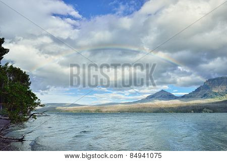 Rainbow In The Cloudy Sky Above Mountains Near The Lake