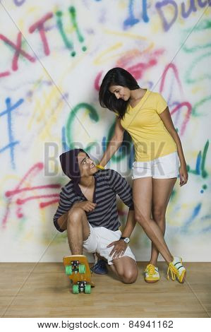 Couple with a skateboard in front of a graffiti covered wall