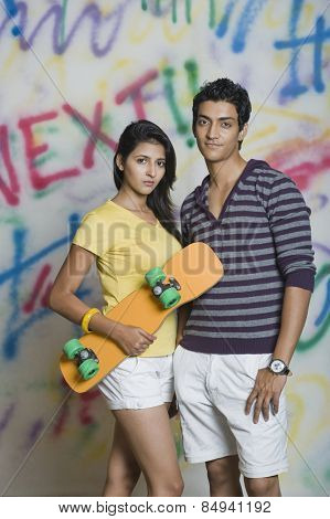Portrait of a couple standing with a skateboard in front of a graffiti covered wall