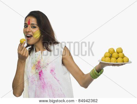 Woman eating Laddu on Holi