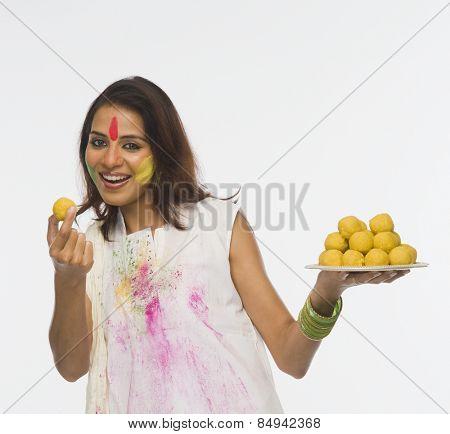 Woman showing Laddu on Holi