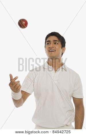 Bowler tossing a cricket ball