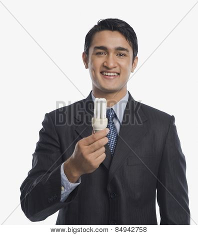 Businessman holding a CFL bulb