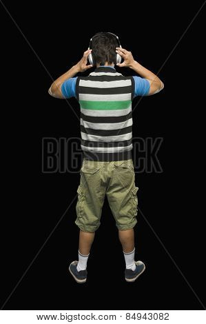 Rear view of a man listening to headphones