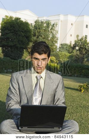 Businessman using a laptop in a park