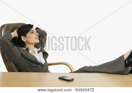 Businesswoman with feet up on a desk