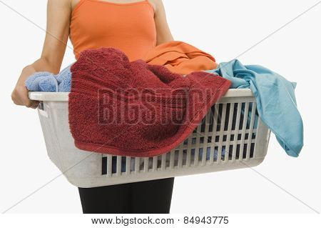 Mid section view of a woman holding laundry basket filled with clothing