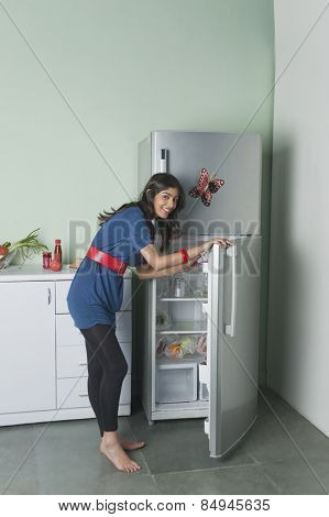Portrait of a woman opening a refrigerator