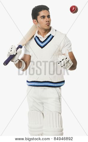 Cricket batsman holding a bat and looking at a ball