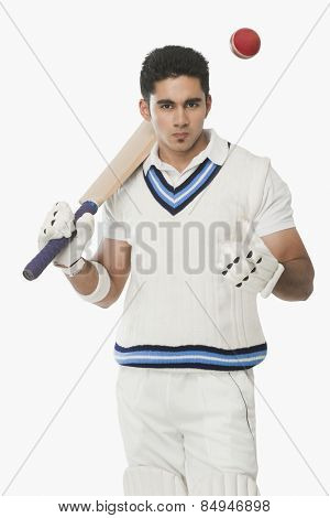 Cricket batsman holding a bat and tossing a ball