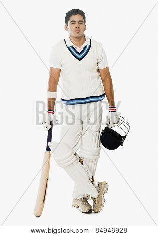 Cricket batsman holding a bat and helmet