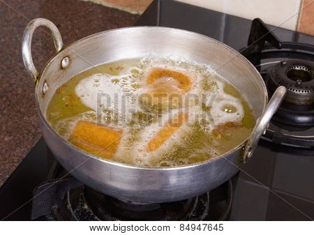 Close-up of pakoras being fried in a pan on a stove