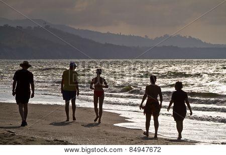 Tourists' silhouettes enjoying the beach in Same, Ecuador