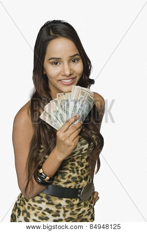 Woman holding currency notes and smiling