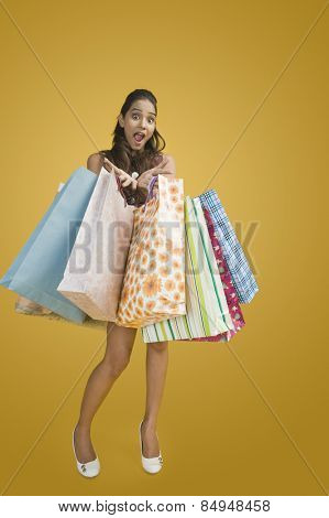 Woman showing shopping bags and looking excited