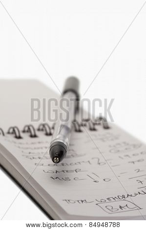 Close-up of a pen on a spiral notebook
