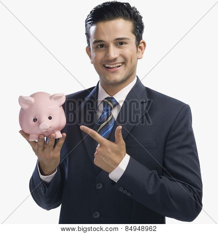 Businessman pointing at a piggy bank