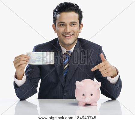 Businessman holding a banknote and pointing at a piggy bank