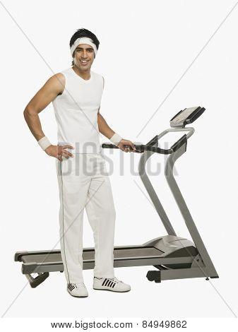 Portrait of a man standing beside a treadmill