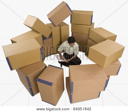 Store incharge sitting with cardboard boxes checking inventory