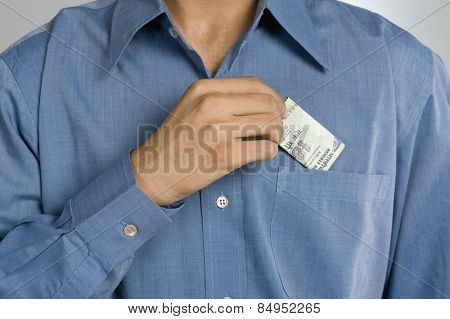 Mid section view of a man putting money in shirt pocket