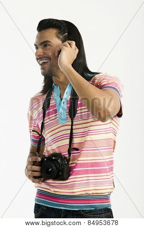 Photographer holding a digital camera and talking on a mobile phone