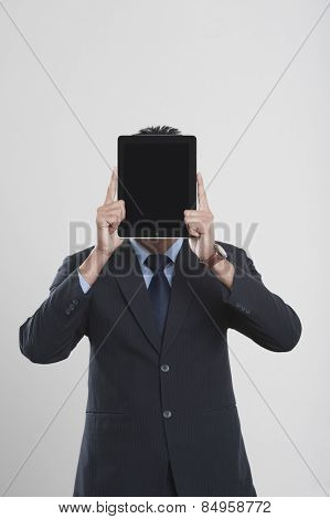 Businessman holding a digital tablet in front of his face