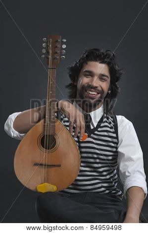 Musician holding a lute and smiling