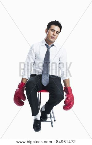 Businessman wearing boxing gloves and looking sad