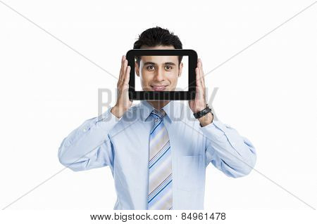 Businessman hiding his face with a digital tablet