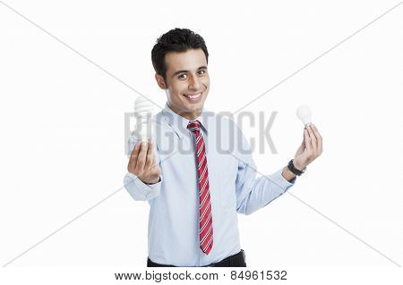 Businessman comparing a light bulb with an energy efficient light bulb