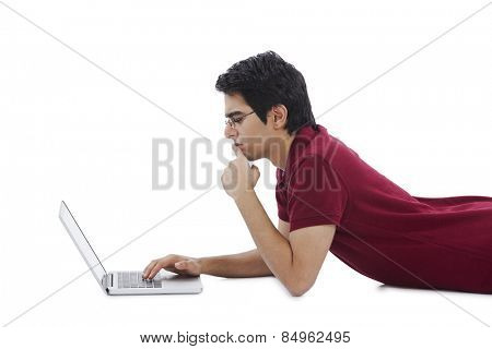 Man lying on the floor and using a laptop