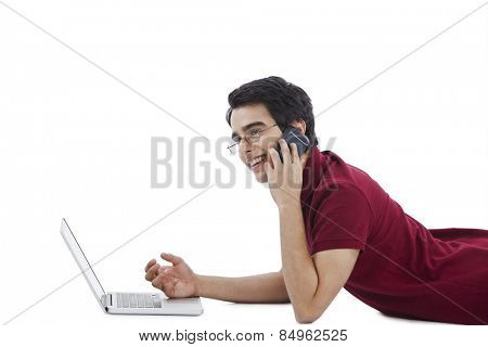 Man lying in front of a laptop and talking on a mobile phone